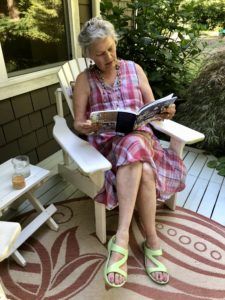 Jennifer sitting in a chair outside reading a book.