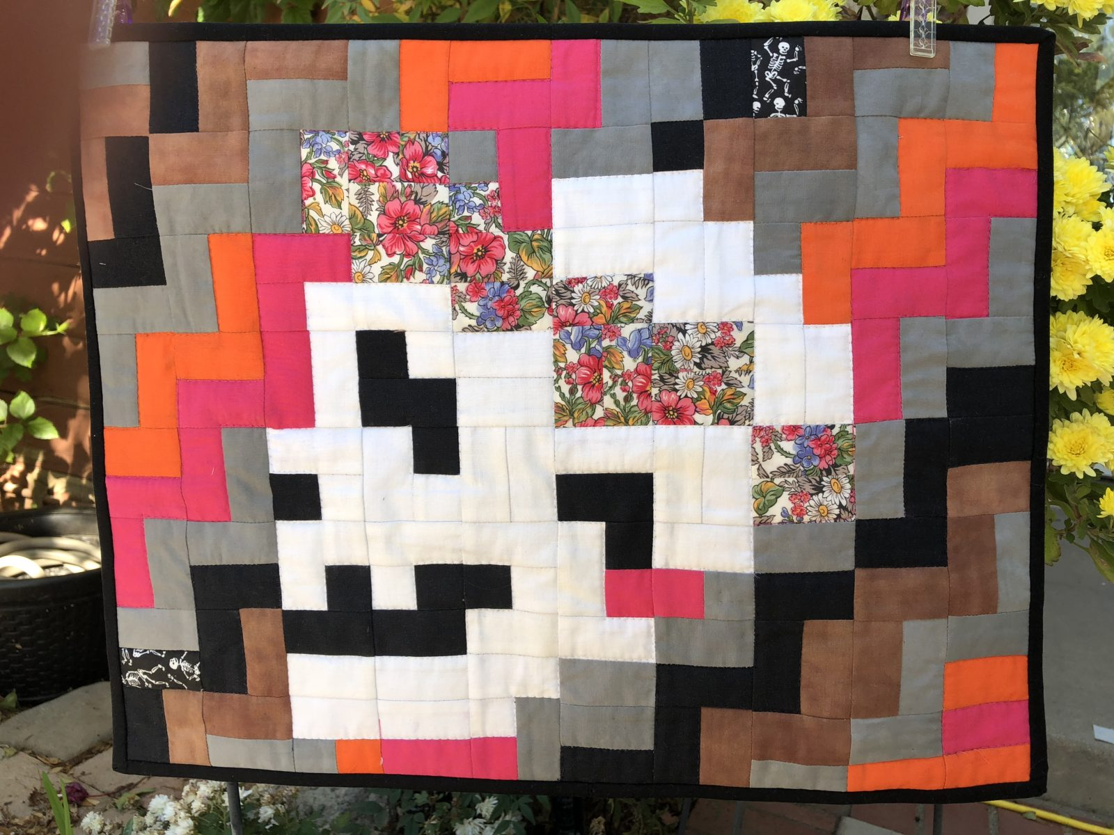 Quilted squares of white, black, pink,, orange with black border